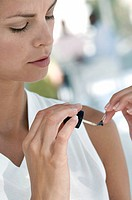 Close_up of a young woman painting her fingernails