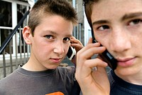 Close_up of two teenage boys talking on mobile phones