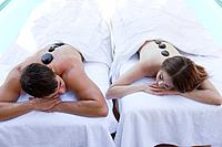 Couple having simultaneous hot stone massages