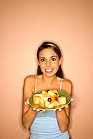 Portrait of young adult woman holding a plate of fruit.