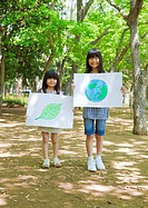 Sisters holding drawings of leaf and globe