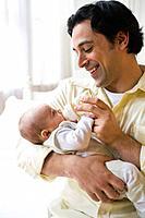 Caucasian father feeding baby son