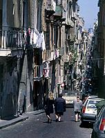 Via pas Scura. Street downtown. Women walking. Buildings. Cars parked. Washing hanging from balconies.