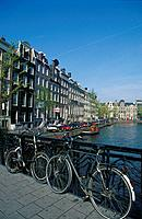 Bicycles on bridge on Herengracht canal. Houses. Trees. Property signs. Cars parked. Boat.