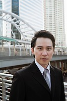 Serious Asian businessman standing outdoors