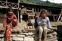 Children outside wooden houses sitting on stone wall. Vashisht traditional rural village in the mountains.
