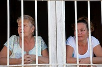 Cuba, Trinidad  Women Watching the Street through their Window Grille