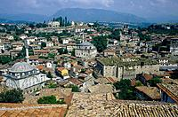 Ottoman town. View over town to west. Two mosques. Traditional style homes. Mountains. Dark sky.