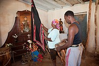 Cuba, Trinidad  Woman Raising Flag in front of Shrine to Saint Anthony San Antonio while Performing an Afro-Cuban Religious Ceremony