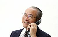 Portrait of Senior Man in Business Suit, Talking on Telephone