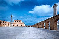Piazza surrounded by arched loggia, with Basilica, lighthouse and Corinthian column on sunny afternoon with stormy sky, Santa Maria di Leuca, Salento,...