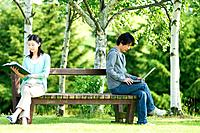 Man and woman sitting on bench in park