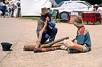 Aborigine playing wooden didgeridoo at craft market. Man sitting watching.