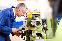 Metalworker using lathe in workshop