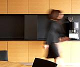 Mid_Adult Businesswoman walking in Kitchen