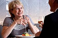 Happy well_dressed senior couple drinking white wine at restaurant