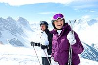 Smiling senior couple with skis on snowy mountain