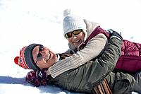 Portrait of smiling senior couple hugging and laying in snow