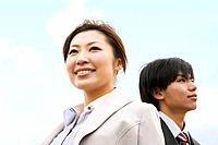 Two Businesspeople Standing Below Blue Sky
