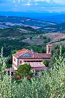 Aerial view of borgo farmhouse with tiled rooftops and church bell tower, fields, hills and distant mountains beyond, sunny late afternoon, Umbria, It...
