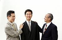 Senior Man and Mid Adult Man Patting on Young Man´s Shoulder