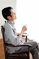 Man with legs crossed at knee holding coffee