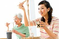 Two women eating soba noodles, smiling