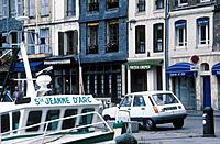Shops and restaurants in street. Boat. Renault car.