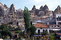 Tufa cave dwellings in rock face. Jagged rock formations. Modern houses.