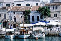 Balearic island. Cuitadella. Waterfront. Boats moored. Buildings. Cafes. Tables and chairs. People.