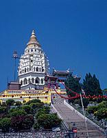 Kek Lok Si Chinese temple. Looking up at temple tower. Yellow walls in front. Steps. Trees. Blue sky