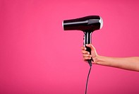 woman hand holding hair dryer on pink background