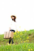 Woman carrying suitcase walking through a meadow