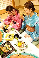 Women wearing yukatas sitting at table with seafood