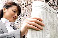 Businesswoman reading a newspaper in a field