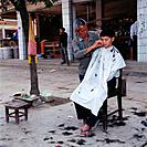 Menghum is a market town in the Xishuangbanna province. Men have their hair cut in the middle of the street on public view.