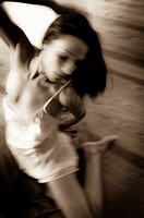 Blurry sepia toned photo of a 27 year old partially nude woman wearing a white chemise & playing with a piece of fabric