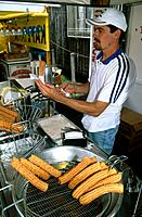 A man making churros,sweet doughnuts with dulce de leche,boiled condensed milk,at a stall.