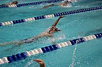 Children race doing the back stroke at a swim meet.