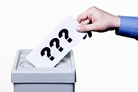 A man putting a ballot with question marks on it into a ballot box, close_up hands