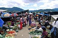 Market. Food stalls. Brightly coloured vegetables. People.