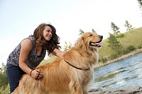 A teenaged Caucasian girl with her Golden Retriever dog at the Spokane River in Spokane, Washington, USA