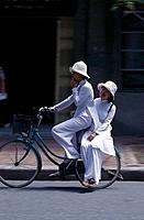 Two young women in white Ao Dai traditional dress. Brilliant white. On bicycle. Hats. DwellingsFood & Drink _ itemsAgriculture