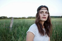 Profile of girl with hair band standing in field looking to the side