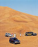 Desert sand dunes. 4 wheel drive vehicules parked on sand. Tracks down steep slopes. People.