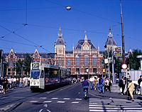 A tram,bicycles and pedestrians outside the Facade of the Neo_Gothic Centraal Railway station which opened in 1889