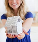 Young woman holding paper house