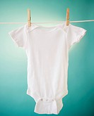 Close up of baby clothes hanging on clothesline