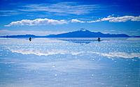 A white salt lake high in the mountains with a shimmering white and blue colours,and reflections of the clouds on the surface of the water. Two people...