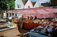 Weekly market. Stalls. Fruit,vegetables. Houses. Painted plaster.